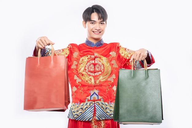 中国の旧正月の買い物から紙袋で男はチャイナドレスのスーツの笑顔を着る 無料写真