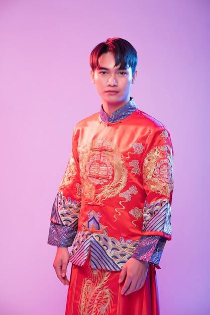 L'uomo indossa cheongsam per accogliere lo shopping dei viaggiatori nel capodanno cinese Foto Gratuite