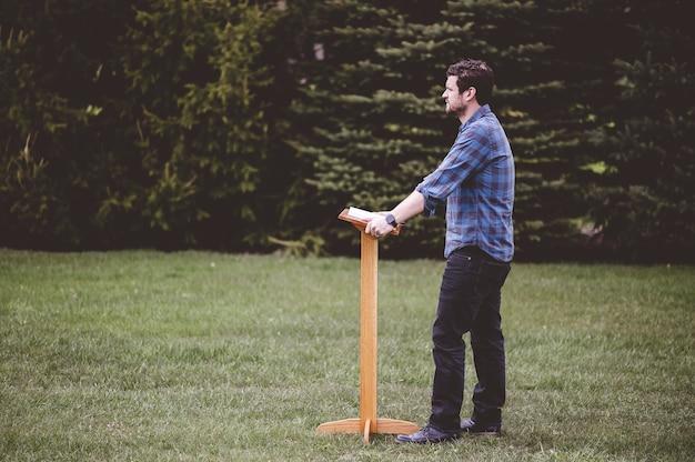 木製の台座の近くに立っている青いシャツを着た男 無料写真