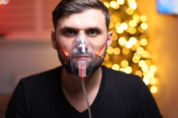 크리스마스 불빛 앞에서 폐 흡입 마스크를 쓰고 남자 프리미엄 사진