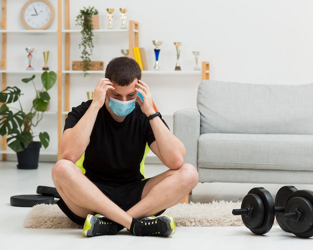 スポーツウェアを着用しながら医療用マスクを着た男 無料写真