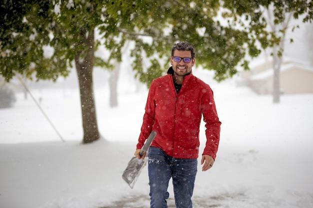 Мужчина в красной куртке гуляет по заснеженному полю, держа лопату для снега Бесплатные Фотографии