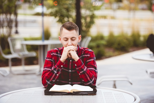 Человек в красной рубашке сидит за столом с открытой книгой в его форме Бесплатные Фотографии