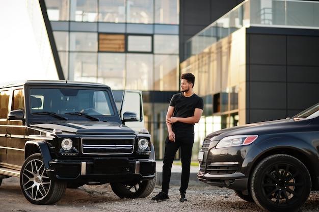 Suvの車の近くでポーズをとってすべて黒を着ている男 Premium写真