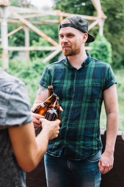 Man wearing cap clinking the brown beer bottles with his friend Free Photo