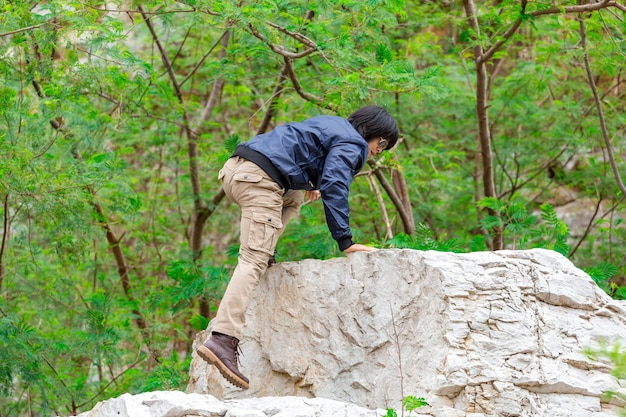Man wearing cargo pants and climbing on the rock Premium Photo