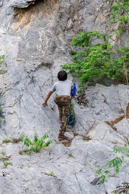Man wearing cargo pants and climbing on the rock Premium Photo