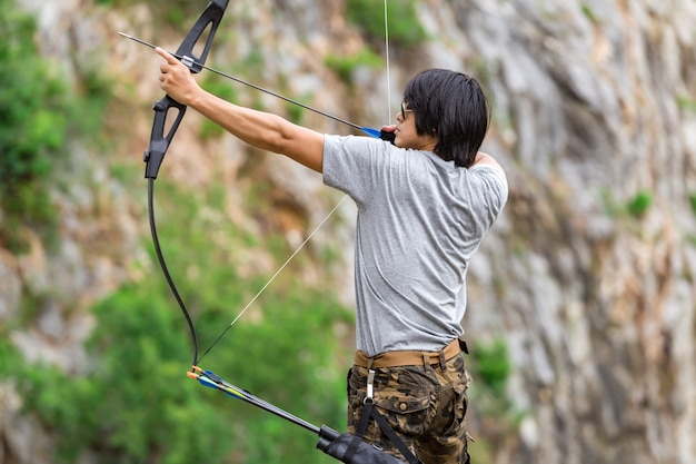Man wearing cargo pants and holding archer Premium Photo