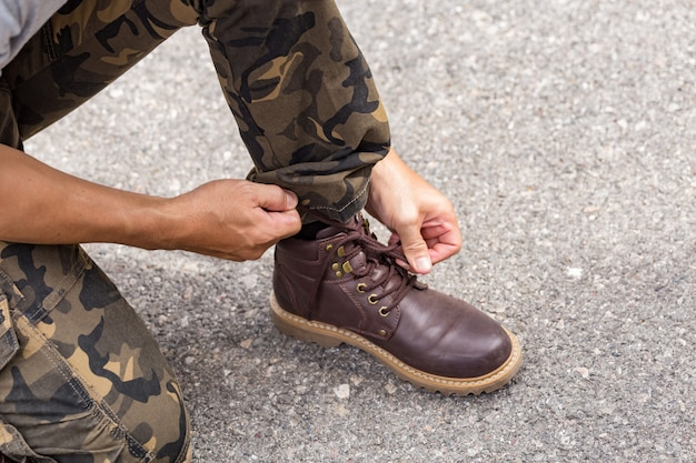 Man wearing cargo pants and tying the laces on leather shoes boot Premium Photo
