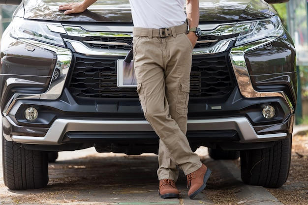 Man wearing cargo pants with suv car parking in the nature park Premium Photo