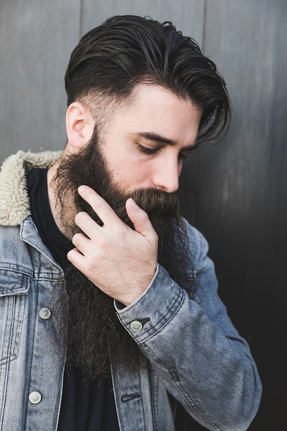 Man wearing denim jacket standing against black surface Free Photo