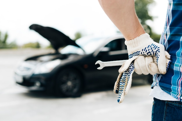Man wearing gloves holding wrench Free Photo