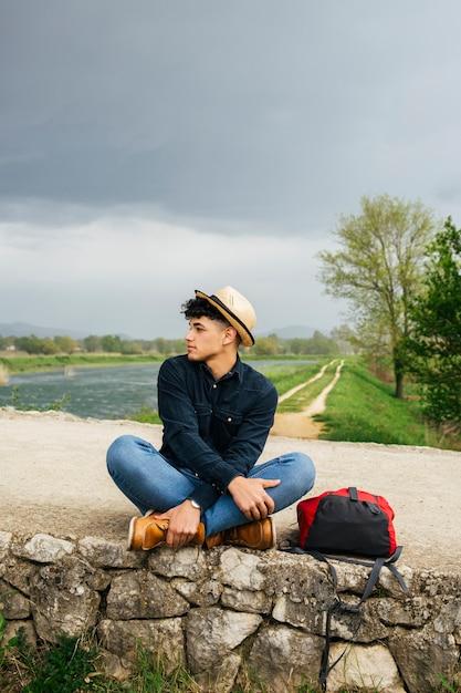 Man wearing hat sitting near beautiful river Free Photo