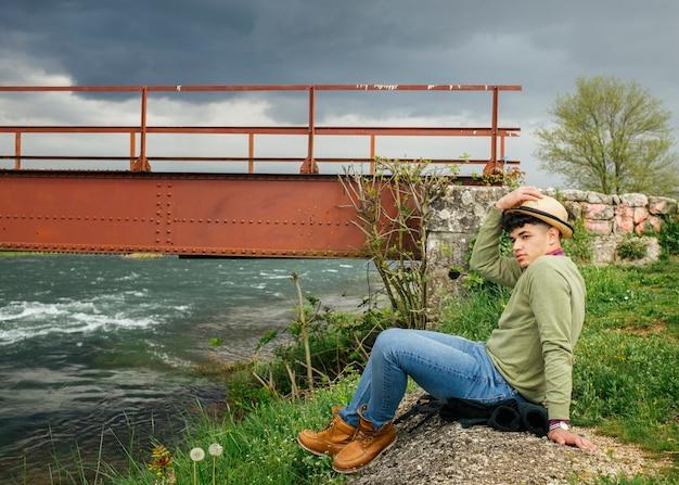Man wearing hat sitting near flower river Free Photo