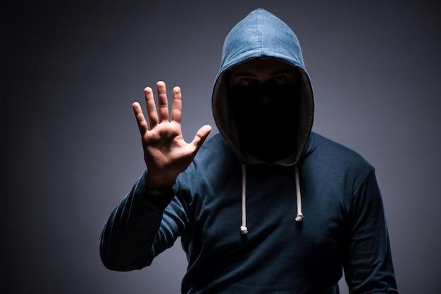 Man wearing hood in dark room Premium Photo