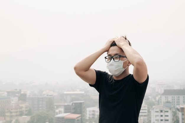 Man wearing hygiene mask and sick because of air pollution in the city. Premium Photo