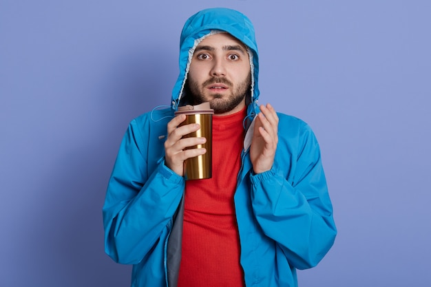 驚いた表情でカメラを直接見て、ジャケットと青い壁にコーヒーを飲む赤いシャツを着た男 無料写真