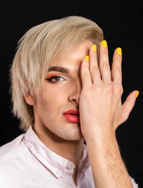 Uomo che indossa il trucco e con le unghie gialle Foto Gratuite