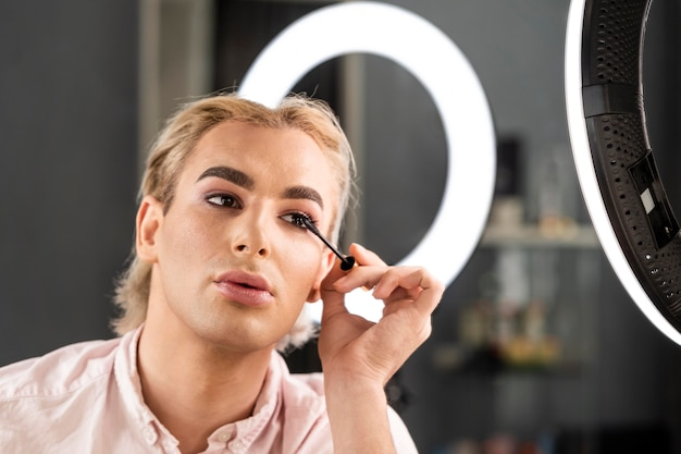 Man wearing make-up using mascara brush Free Photo