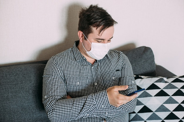 Man wearing mask working with smartphone working from home office Premium Photo