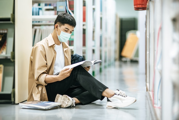 A man wearing masks is sitting reading a book in the library. Free Photo
