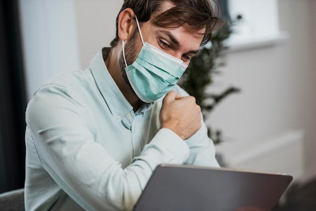 職場で医療用マスクを着用している男性 無料写真