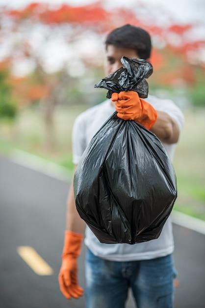 Un uomo che indossa guanti arancioni raccogliendo immondizia in una borsa nera. Foto Gratuite