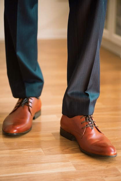 Man wearing shoes on wooden floor. clothing concept, groom getting ready before ceremony. body detail of businessman. Premium Photo