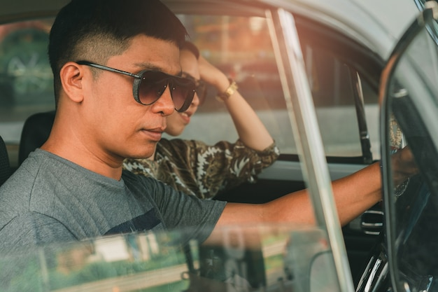 Man wearing sunglasses driving car vintage with female on street Premium Photo