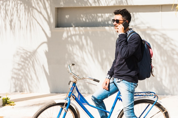 Man wearing sunglasses sitting on blue bicycle talking over his mobile phone Free Photo