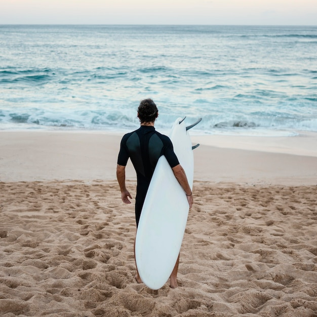 Man wearing surfer clothes walking on the sand from behind Free Photo
