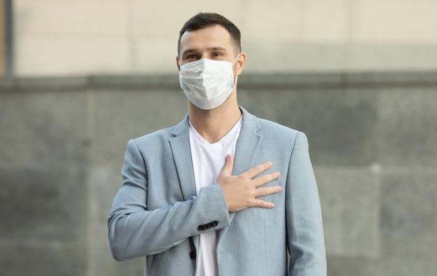 Мужчина в хирургической маске приветствует рукой над сердцем Premium Фотографии