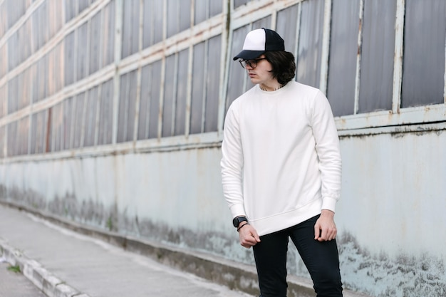 Man wearing white sweatshirt or hoodie, baseball cap and glasses outside on the city streets. Premium Photo