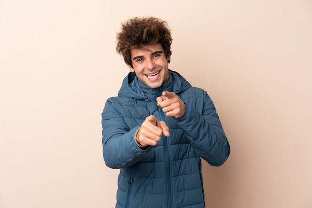 Man wearing winter jacket over isolated wall points finger at you with a confident expression Premium Photo