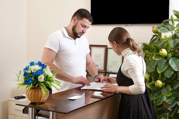 사무실 리셉션 데스크에서 젊은 여자 클라이언트를 환영하는 남자 프리미엄 사진