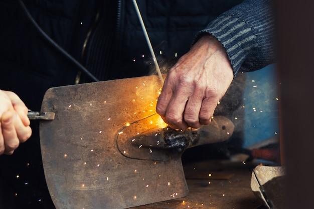 Человек сваривая старый лопаткоулавливатель, конец вверх. Бесплатные Фотографии