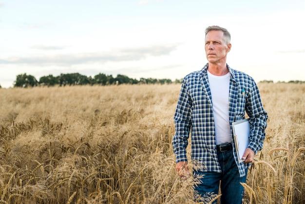 Man in a wheat field looking away Free Photo