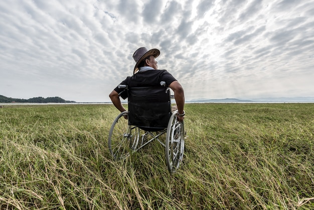 Man on a wheelchair relaxing in a park Premium Photo
