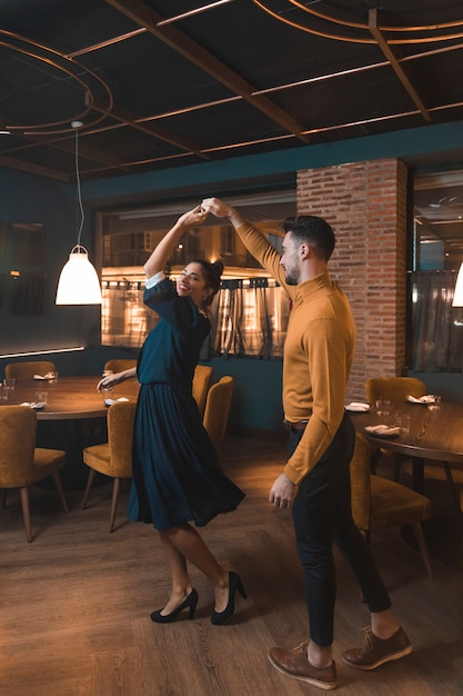 Man whirling cheerful woman in restaurant Free Photo