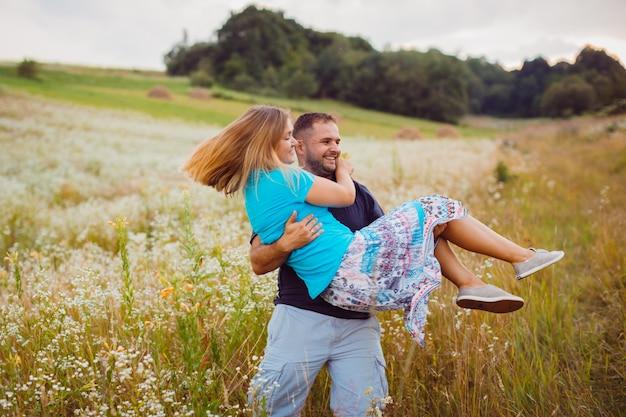 Человек whirls блондинка женщина на руках, стоя на поле Бесплатные Фотографии