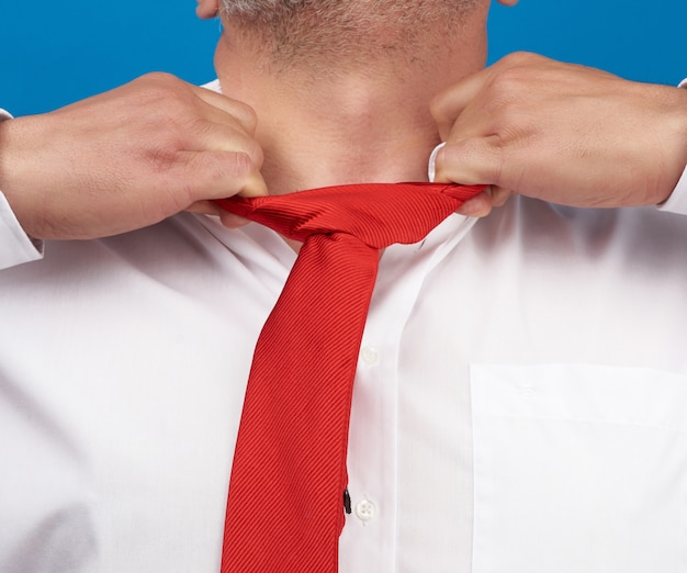 Man in a white office shirt tears off a red satin tie from his neck Premium Photo