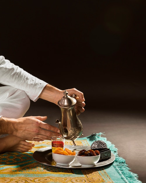 Man in white pouring tea in tiny cup front view Free Photo