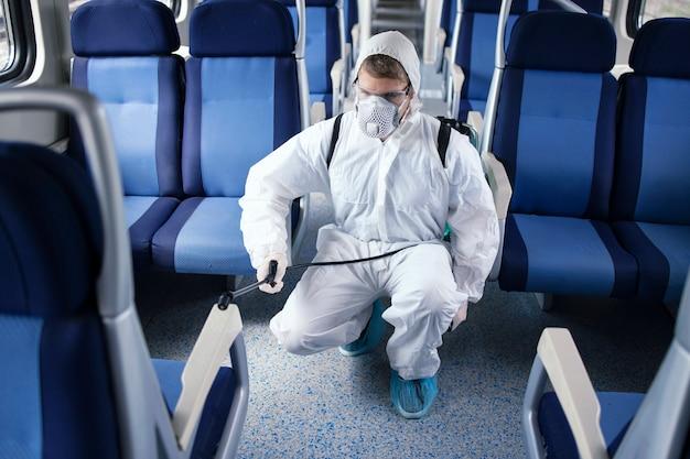 Uomo in tuta di protezione bianca che disinfetta e igienizza l'interno del treno della metropolitana per fermare la diffusione del virus corona altamente contagioso Foto Gratuite