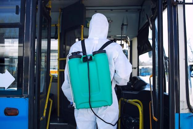 Uomo in tuta protettiva bianca con serbatoio che entra in autobus per spruzzare disinfettante a causa della pandemia globale del virus corona Foto Gratuite