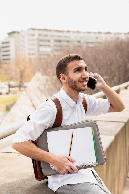 Man in white shirt talking on phone and looking up Free Photo
