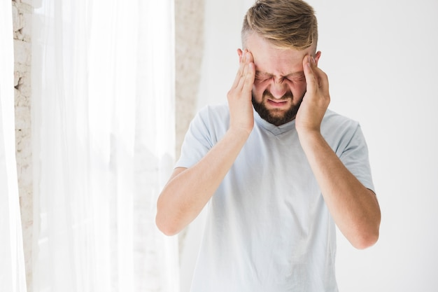 Man in white suffering from pain Free Photo