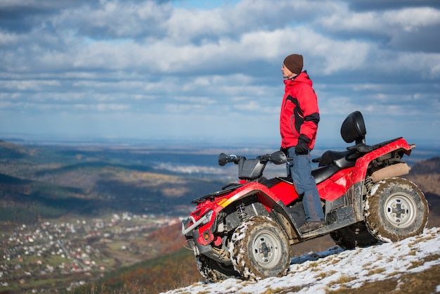 Man in winter clothes standing on a red quad bike Premium Photo
