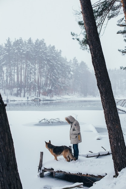Uomo in cappotto invernale nella foresta con cane da pastore Foto Gratuite