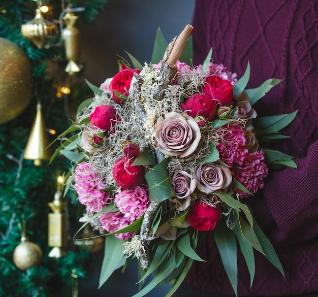 Man in winter outfits with a bouquet of mixed flowers Free Photo