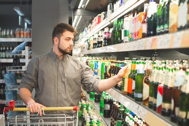 Мужчина с бородой покупает пиво в супермаркете, берет бутылку с полки в алкогольном отделе Premium Фотографии